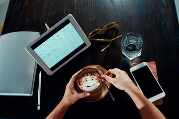 Businesswoman sitting at the table around wireless devices and enjoying a cup of delicious coffee