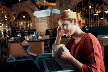 Side view of pretty young woman using wi-fi free and communicating on laptop while drinking coffee at the restaurant