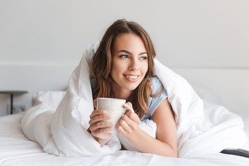 Smiling young woman holding mug while laying in bed