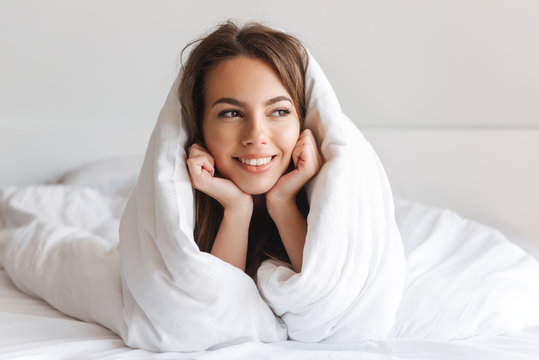 Happy young woman laying in bed covered