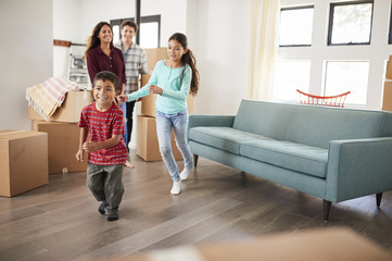 Excited Family Surrounded By Boxes Exploring New Home On Moving Day