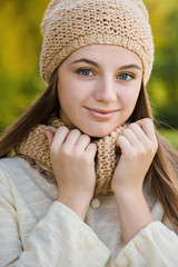 Nice female portrait in knitted hat and scarf in autumn park