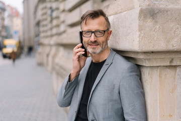 Middle-aged man smiling while talking on mobile