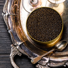 Black caviar in can and champagne on silver tray on black wooden background close-up