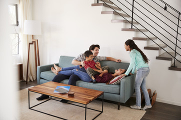 Family Having Fun Lying On Sofa At Home Together