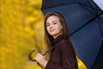 Girl hold umbrella on yellow autumn leaves background