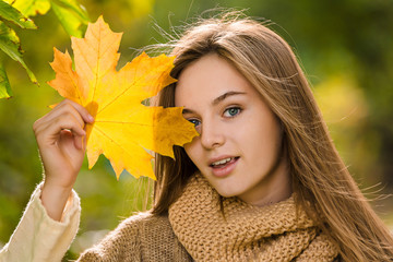 Young pretty girl portrait with yellow mapple leaf closed face by autumn bouquet