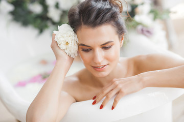 Perfact woman bathing with flowers and milk