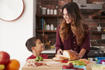 Mother And Son Making School Lunch In Kitchen At Home