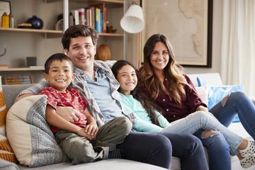 Portrait Of Happy Family Relaxing On Sofa At Home Together