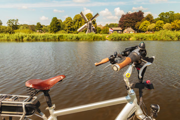 Electric bicycle in front of a Dutch river with a windmill