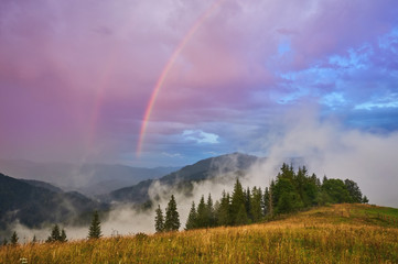 Mountain nature photo background with bright rainbow