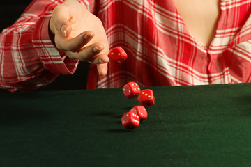 Girl rolling red dice fall on a table
