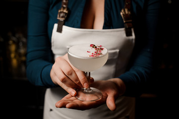 Bartender girl holding a white cocktail decorated with dried flowers