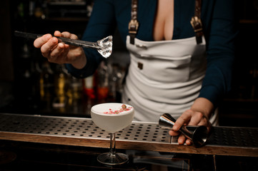 Bartender girl adding ice to a white cocktail decorated with dried flowers