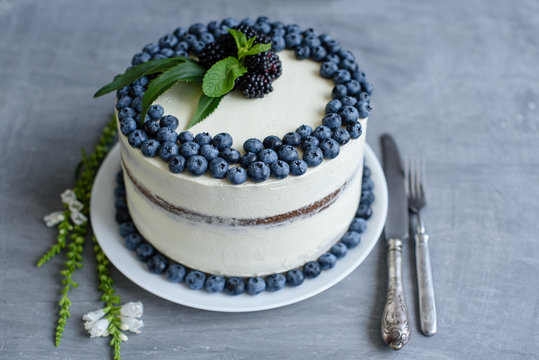 Beautiful tasty cake with white cream and berries of blueberry
