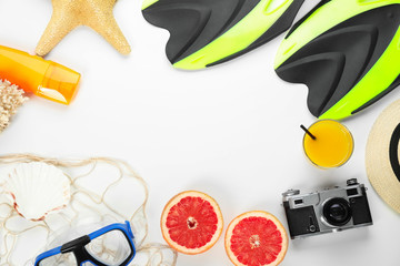 Composition with beach accessories and photo camera on white background