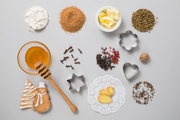 Christmas gingerbread cooking ingredients. Flour, sugar, butter, honey and spices on a gray background. Top view