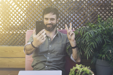 Content attractive man in stylish clothes photographing himself on mobile phone and showing peace gesture.Bearded hipster making selfie via smartphone on terrace outside.