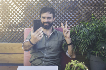 Content confident man in stylish clothes photographing himself on mobile phone and showing peace gesture.Bearded hipster making selfie via smartphone on terrace outside.