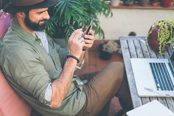 Bearded confident hipster wearing green shirt and brown hat texting message via smartphone on terrace outside. Positive man relaxing at summer day