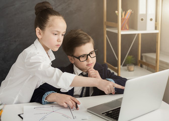 Little boy and girl working on laptop