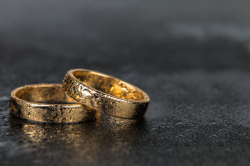 Wedding rings with water drops on dark background with copy space.