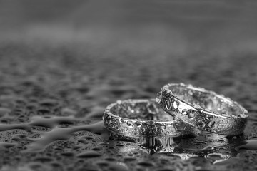 Wedding rings with water drops on grey background with copy space.