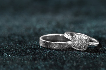 Two wedding rings on dark velvet background with copy space.
