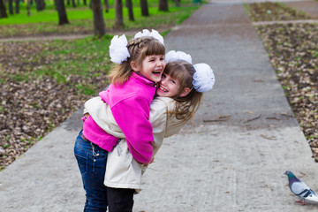 Two funny siblings sister hugging with each other while walk in park. Having fun together, positive emotions, bright colors. Copy space. Back to school