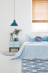 White bedroom interior with blue bedding on double bed, navy lamp, bedside table with clock and plant and carpet on the floor
