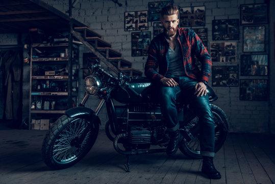 Bearded Biker Sitting on Motorcycle in Garage.
