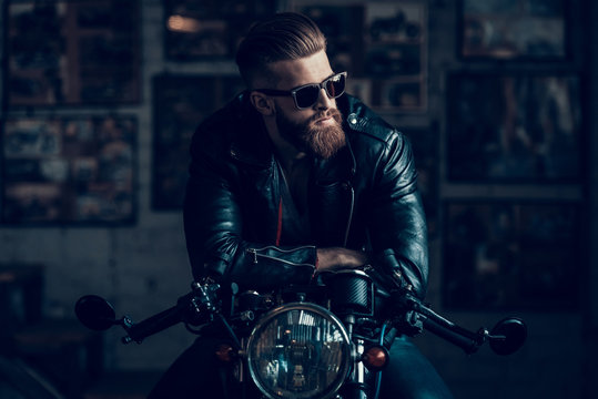 Young Biker in Sunglasses on Motorcycle in Garage.