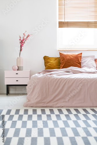 Bed with pink sheets and orange cushions standing in white bedroom ...