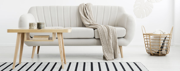 Wooden coffee table with books and two marble boxes standing on striped carpet in real photo of bright living room interior with blanket in wicker basket and light grey lounge