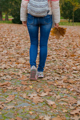 girl is walking in the autumn park.  tourist woman walks with a backpack over an autumn park with fallen leaves