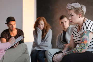 Tattooed rebel teenage girl sitting in front of a therapist who is taking notes during a group psychotherapy meeting. Other young people in the blurred background.