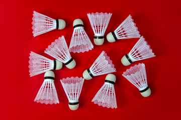 Badminton shuttlecocks against a red background