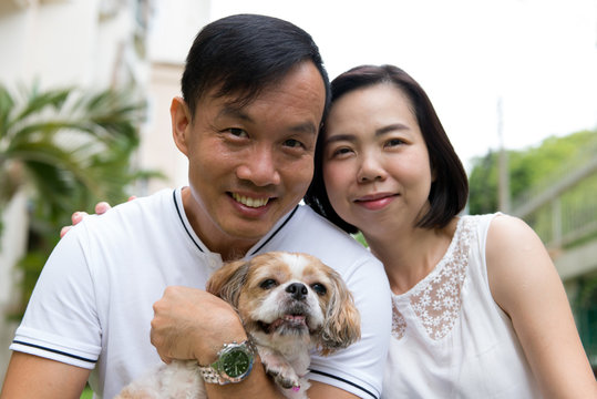 Lovely asian couple with their pet shih tzu puppy at outdoor park