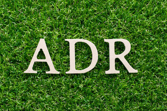 Wood alphabet in word ADR (Abbreviation of adverse drug reaction) on artificial green grass background