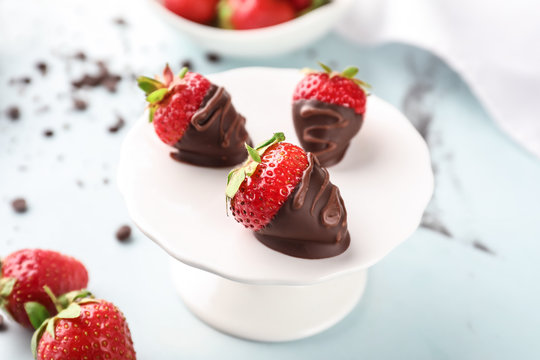 Dessert stand with delicious strawberries dipped in dark chocolate on color background