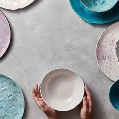 Colorful porceain vintage handmade dishes on a marble table with copyspace. Woman hands take a white ceramic bowl. Top view.