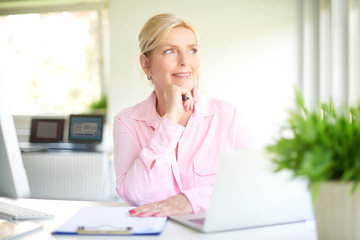 Attractive smiling businesswoman looking thoughtfully
