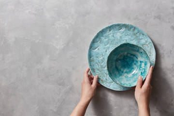 Vintage painted glazed plates dishes on gray concrete table with free space ror text. Girl hold handcraft bowl in her hand. .