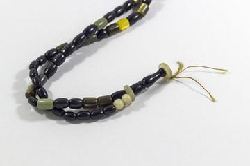 Close-up detail shot of handmade black and green stone islamic prayer beads