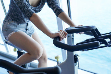 Close-up women working out in gym on the exercise bike,