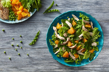 Fresh salad with orange fruit, greens, chicken on blue plate on a gray wooden table. Flat lay.