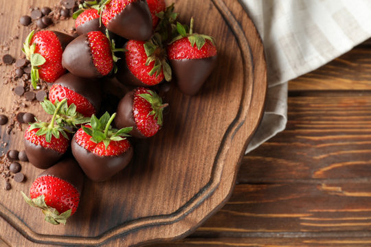 Board with tasty chocolate dipped strawberries on wooden table