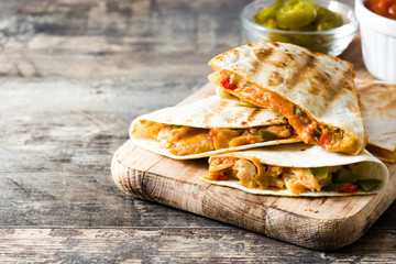 Mexican quesadilla with chicken, cheese and peppers on wooden table. Copyspace