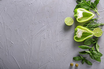 Fresh herbs with pepper and cut lime on grey textured background